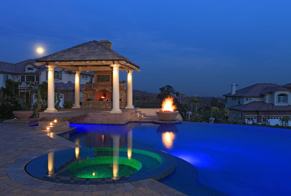Outdoor Fireplace And Swimming Pool With Lighted Spa And