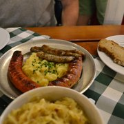 Assorted grilled sausages with potato salad, sauerkraut in the foreground