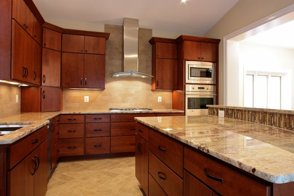 Kitchen with a curved, granite countertop island, stainless