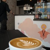 a flat white, the frequent drinker wall, and one of the nice guys who makes good coffee