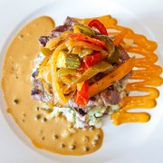 Char-grilled Lamb Steak on a bed of Crushed New Potatoes, served with Julienne Vegetables and a Green Peppercorn Sauce