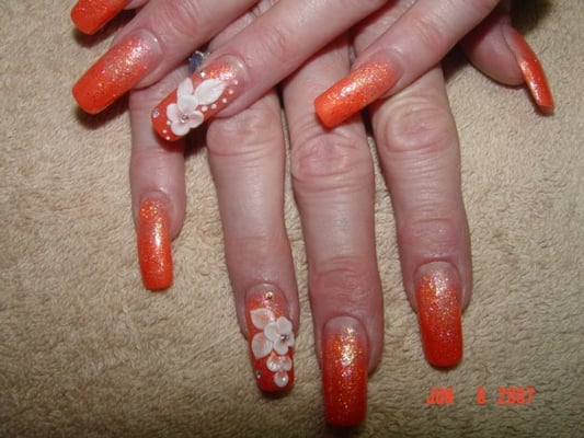 Orange Fade with 3D art. Flower design done by hand using nail acrylic